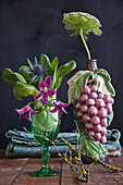 Unusual arrangement of clematis, sea holly and pak choi in wine glass and bishop's flower in ceramic vase