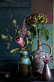 Vases of hydrangeas, protea, astilbes and sea holly 'Supernova'