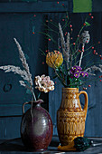 Autumn bouquets of carnations, pincushion, chrysanthemums, rose hips, poppy seed heads and grass seed heads in vintage jugs