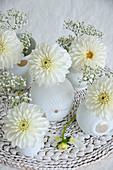 Dahlias and gypsophila in white vases