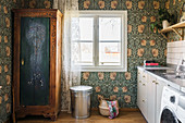 Old wardrobe in laundry room with vintage-style floral wallpaper