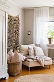 Fur blanket on easy chair below wall hanging in Bohemian-style living room