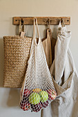 Net shopping bag of apples, raffia basket, chopping boards and apron hanging from row of hooks