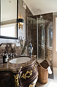Opulent, Baroque washstand with stone top in classic bathroom