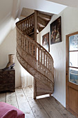 Shabby-chic spiral staircase on rustic wooden floor