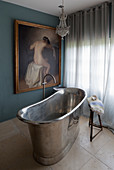 Freestanding, metal bathtub and classic painting in bathroom