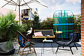 Designer furniture on balcony screened by plants