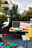 Stork ornament on balcony screened by plants