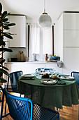 Gedeckter Tisch mit blauen Stühlen in kleiner Wohnküche