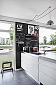 Chalkboard wall in modern kitchen with floor-to-ceiling windows