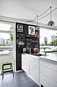 Schwarze Wand im Tafel-Stil in moderner Küche mit bodentiefen Fenstern