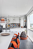 Dining table and orange chairs in front of modern, open-plan kitchen