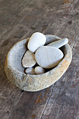 Pebbles in stone bowl on wooden floor