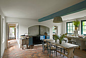 Dining table and terracotta floor tiles in rustic country-house kitchen
