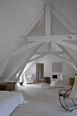 Simple, white attic room with rustic roof beams