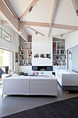 White living room with high ceiling and pale wooden beams