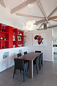 Upholstered chairs around table next to red shelves in modern dining room
