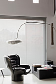Arc lamp above black designer armchair next to window