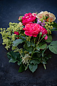 Roses, lady's mantel and hydrangeas on dark surface