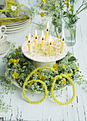 Wreath of cow parsley and buttercups on plate around candles on cake stand for 60th birthday