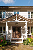 Wooden house in American country-house style with porch and veranda