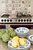 Quinces, artichokes and plates on stainless steel table in kitchen