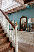 Runner with bold pattern on staircase in hallway with curiosities on sideboard