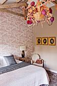 Eccentric chandeliers in shades of pink in bedroom with toile de jouy wallpaper