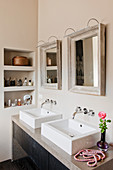 Two mirrors above square twin sinks in beige bathroom