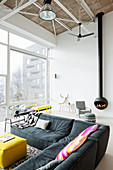 Grey corner sofa in modern living room of loft apartment with suspended fireplace