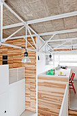 Desk on gallery in modern loft apartment with wood-clad walls