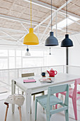 Industrial lamps above dining table and colourful chairs in loft apartment
