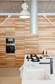 Fitted cupboards with wooden doors in modern kitchen in loft apartment