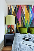 Double bed and lamp on bedside table against wall with multicoloured graphic pattern