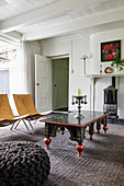 Antique table and modern chairs in front of wood-burning stove