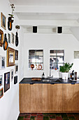 Collection of pictures on white wall and view of kitchen counter