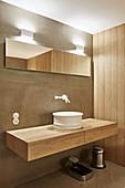 Sink on floating wooden washstand in bathroom