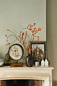 Sprigs of berries, geode and vintage ornaments on mantelpiece