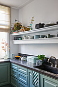 Classic kitchen with blue-green panelled cabinets