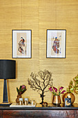 Japanese prints above golden ornaments and corals against grasscloth wallpaper