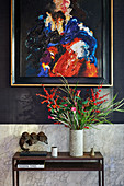 Abstraktes Gemälde an schwarzer Wand überm Konsolentisch