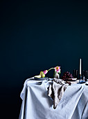 Pale tablecloth, pear, flower and grapes on dining table