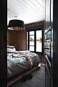 View through open panelled door into rustic bedroom