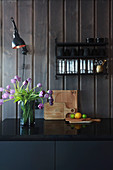 Vase of tulips on black kitchen counter against wood-clad walls