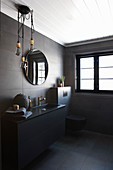 Modern, masculine bathroom decorated in black with golden accents