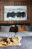 Picture of two musk oxen above bed with bed linen in earthy shades