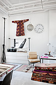 Classic chair, stack of kilim rugs and kimono hung on wall in white-painted study