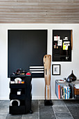 Eames' Leg Splint sculpture, black pinboard and trolley in study