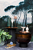 Ornaments on tables against mural wallpaper with landscape motif