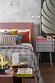 Scatter cushions on double bed, bedside cabinet and tray and jug on bedroom bench